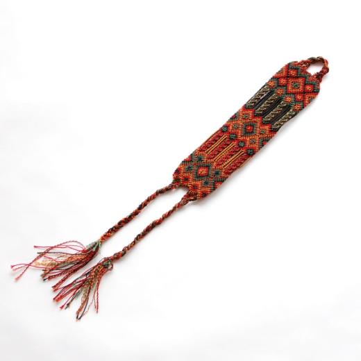 Ručně vyrobený náramek z barevných šňůrek tmavších barev zobrazuje typické obrazce pro oblast Chamuly, Chiapas.