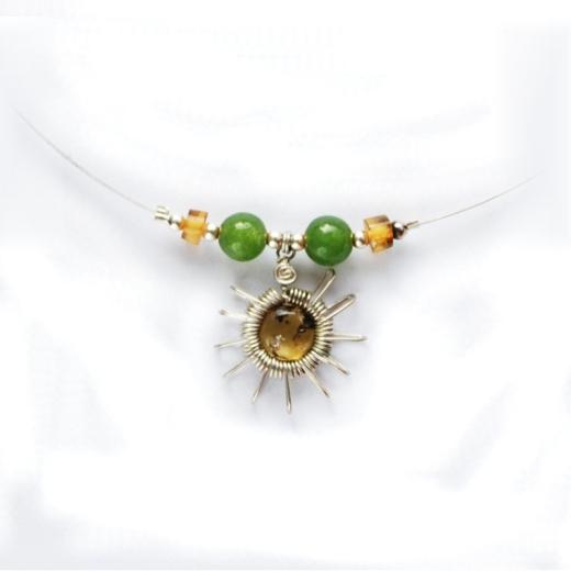 Náhrdelník je z velmi tenkého pružného drátku se dvěma světle zelenými korálky a drátěným sluncem, v jehož středu je kulatý jantar.