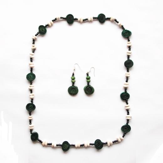 Sada náhrdelníku a náušnic ze sušené kůry pomeranče stočené do spirály a nabarvené na zelenou barvu. Mezi spirálkami kůry jsou bílé fazolky a malé tmavé korálky.