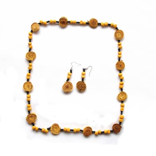 Sada šperků ze sušené kůry pomeranče stočené do spirály a nabarvené na žluto. Sada šperků obsahuje náušnice a náhrdelník. Mezi spirálkami kůry jsou semínka kukuřice.