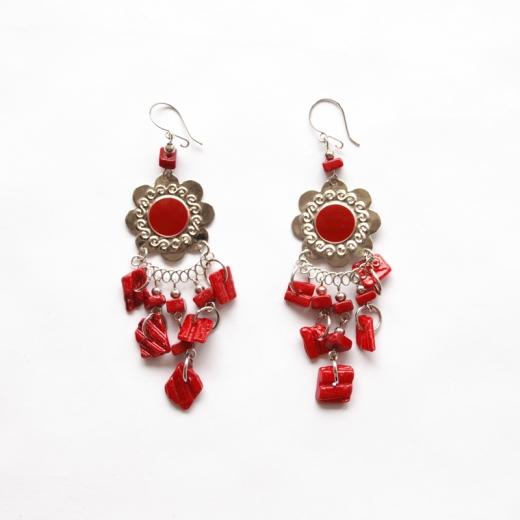 Náušnice s lesklým plíškem ve tvaru květu s červeným středem. Červené kamínky volně z náušnice visí na řetízcích.