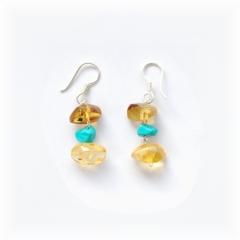 Náušnice mají na řetízku zavěšené dva oblé valouny ze žlutého jantaru a uprostřed je tyrkysový minerál turquesa.